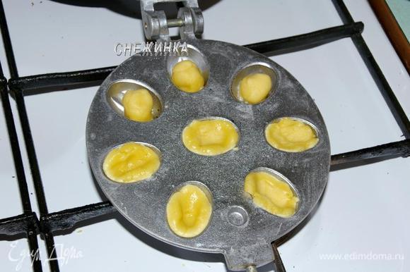 Теперь можно заняться выпечкой «орешков». Форму, как и в предыдущем варианте, разогреваем с двух сторон. Для этого печенья форму смазывать не нужно, тесто прилипать не будет. Отщипываем от теста маленькие шарики, немного разминаем под размер выемки. Накрываем второй половиной формы и печём на огне. Помните, что половинки «орешков» пекутся быстро, в этом варианте тесто получается тонкое, уже через минуту-полторы следует переворачивать форму, поэтому лучше не отходить. И, как прежде, проверяйте, раскрывая форму.