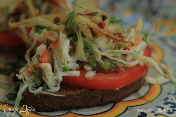 На тосты выложить кружки помидора, мясо крабов и обжаренный фенхель.