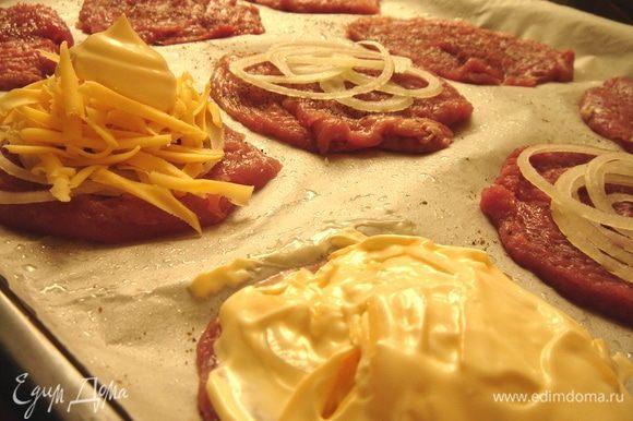Выложить на противень кусочки мяса. Посолить и поперчить их с одной стороны. Лук тонко нарезать кольцами или полукольцами, сыр натереть на крупной тёрке. На мясо выложить лук, затем сыр и покрыть эту пирамиду майонезом.