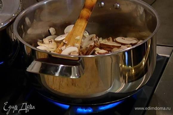 В кастрюлю к грибам добавить чеснок, часть листьев тимьяна, перемешать и продолжать обжаривать на медленном огне, не накрывая крышкой.