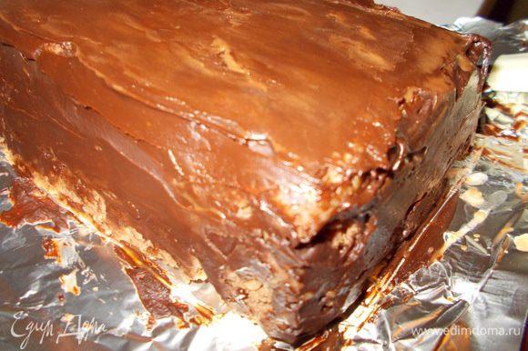 Достаем наш торт из холодильника.Выкладываем его на доску,предварительно сняв целлофановую пленку.Освобождаем торт от фольги и покрываем его глазурью.Глазурь застывает очень быстро,поэтому наносить её нужно оперативно :)).Чтобы выровнять поверхность глазури,окунаем узкую металлическую лопатку в горячую воду и плоской поверхностью разглаживаем её.Если глазурь легла полосками,это очень хорошо потому,как торт будет больше похож на полено.:)).