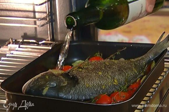 Рыбу натереть снаружи и изнутри маринадом, выложить на картофель с помидорами и запекать в разогретой духовке 5–10 минут, затем полить рыбу вином и запекать еще 15 минут.