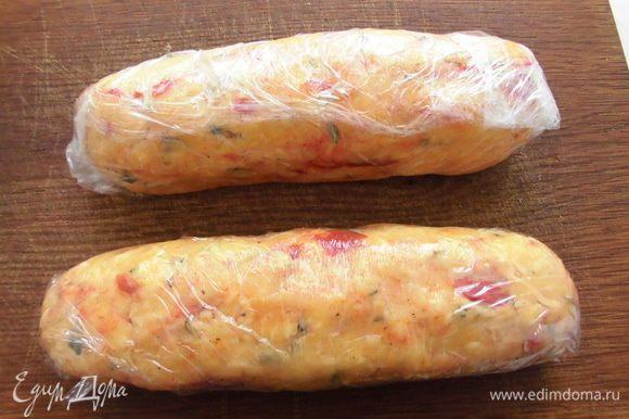Добавить сыр, перемешать ложкой. Всыпать вяленые помидоры и измельченный розмарин. Снова перемешать. Положить желтки и вымесить тесто. Сделать из него 2 колбаски, завернуть в пищевую пленку и отправить в холодильник на 1 час.