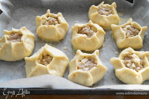 Выложить наши пирожки на противень, застеленный бумагой для выпечки и смазанный маслом, смазать их желтком, и поставить выпекать в разогретую до 180 градусов духовку на 15 минут