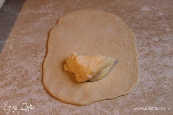 Готовое тесто кладем на рабочий стол, делим его на 15 кусочков и раскатываем каждый кусочек овалом около 12 см. На край лепешки кладем ложку нашей начинки, крема.