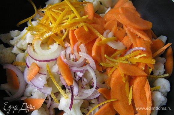 В сотейник с толстым дном выложить капусту, морковь, лук и цедру. Залить половиной соуса и варить 10-12 минут до готовности.