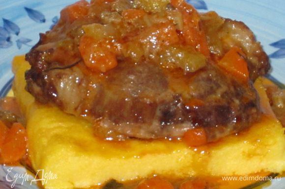 Мясо выложить на поленту и полить мясным соусом.