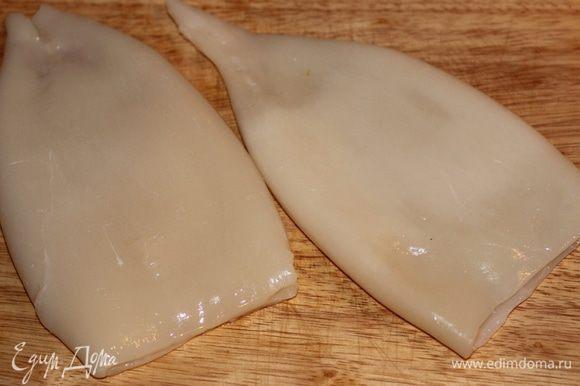 Тушки кальмаров очистить от тонкой внешней пленки, аккуратно поддевая ее пальцами и стараясь не порвать - целиком она легче снимается. Промыть водой, тщательно обсушить бумажными салфетками.
