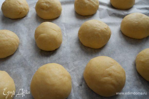 Разделите тесто на 12 равных частей, скатайте ровные шарики, выкладывайте на противень, застеленный пекарской бумагой. Дайте время булочкам подойти, около 30 минут.