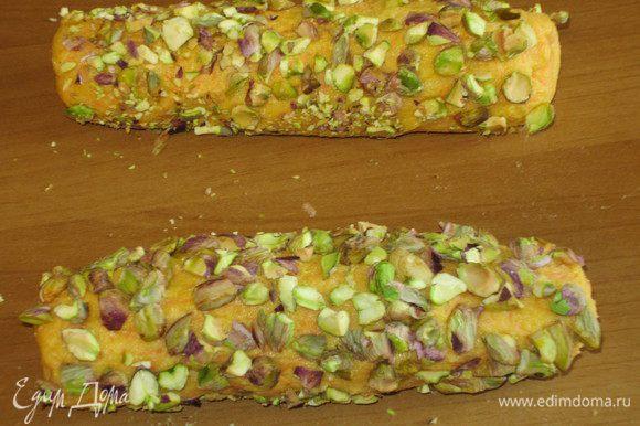 Сформировать 2 колбаски диаметром 3 см. Высыпаем на рабочую поверхность измельчённые фисташки, обваливаем со всех сторон, заворачиваем в плёнку и отправляем в холодильник на 1 час.