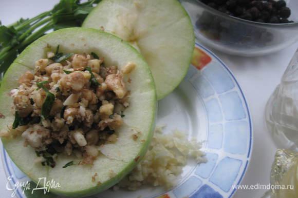 Яблоко помыть, срезать крышечку, из основной части вынуть частично мякоть, семечки. 2 зубчика чеснока, соль, измельченную петрушку размять в ступке. Наполнить этой смесью яблоко, закрыть крышечкой.