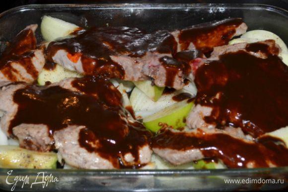 Выложить свиные отбивные поверх яблок и шалота. Вылить половину барбекю сверху. Поставить в духовку снизив тем-ру на 190 гр. на 15 мин. Перевернуть, вылить вторую часть соуса барбекю и готовить еще 15 мин. или до готовности.