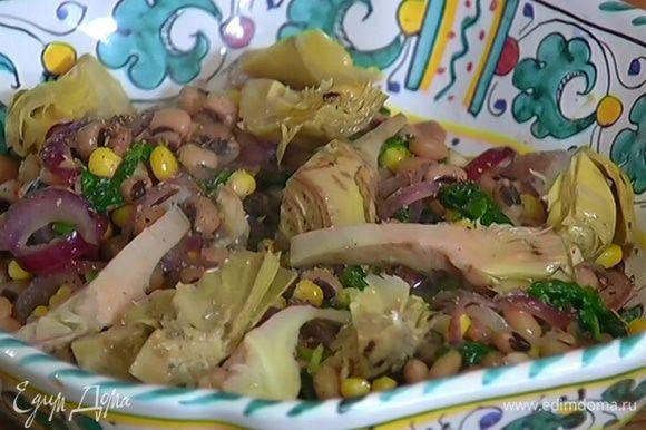 Салат выложить в глубокое блюдо, посолить, поперчить, выложить сверху артишоки и сразу подавать.