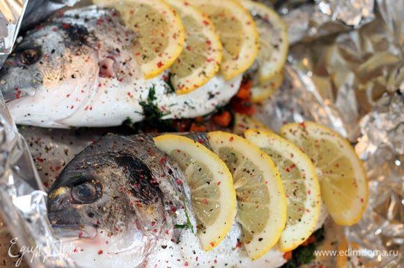 Рыбу чистим, моем, вытираем бумажным полотенцем. Мелко рубим зелень, режем кубиками морковь и болгарский перец. Рыбу натираем солью и смесью перцев, фаршируем смесью рубленной зелени и овощей. Укладываем слоями: лимоны, фаршированная рыба, лимоны. Кладем по кусочку масла на рыбу, поливаем вином. накрываем фольгой и отправляем в духовку на 10 минут при 200 градусах. Затем убираем фольгу, увеличиваем температуру и ждем появления золотистой корочки 3-5 минут.