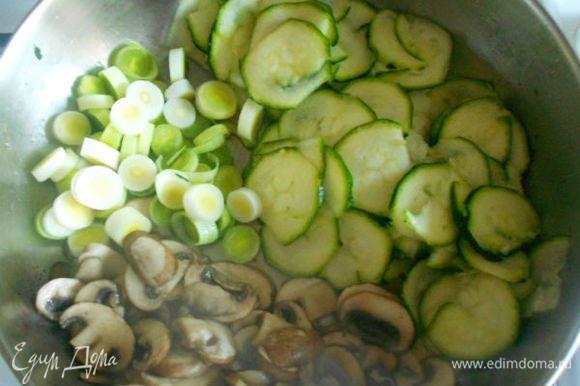 Сдвинуть грибы в сторону и обжарить до мягкости нарезанный колечками (шайбами) порей и натёртый на тёрке кружочками цукини.