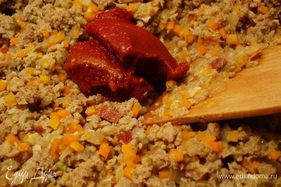 Добавляем томатную пасту, перемешиваем, обжариваем