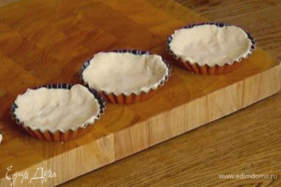 Тесто разрезать на 4 части и выложить в небольшие формы, равномерно распределив по дну и бортикам.