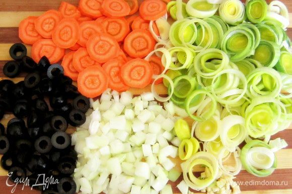 Морковь нарезать кружочками, лук порей нарезать кольцами, репчатый лук и чеснок мелко порезать, маслины порезать пополам.