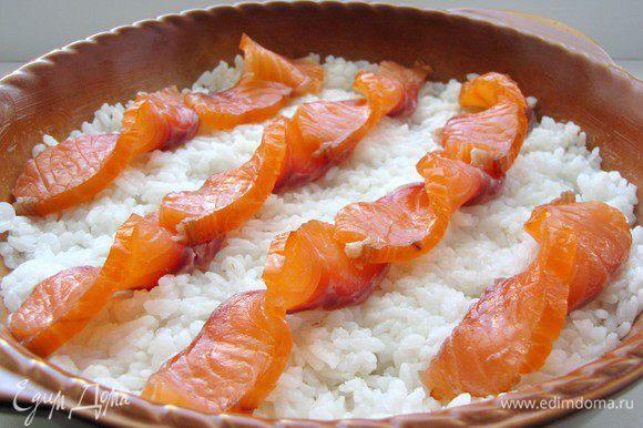 Лосося нарежьте тонкими ломтиками и выложите на рис.