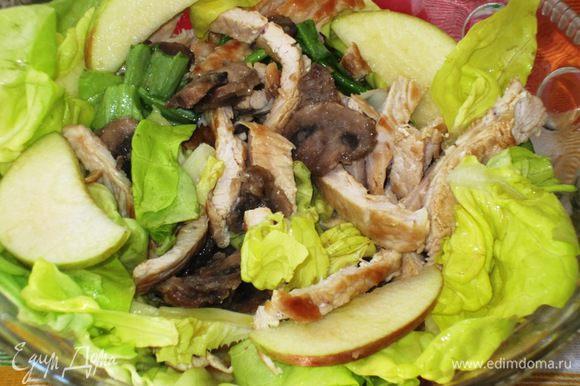 Заправить листья салата и яблоки, выложить на блюдо.Сверху выложить кусочки индейки и грибы.Приятного аппетита:)