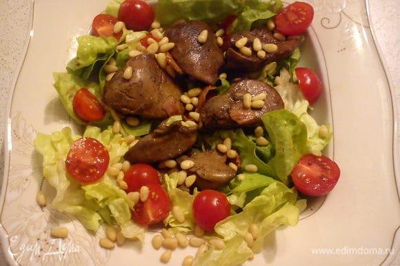 Листья салата порвать руками и выложить на тарелку. На листья выложить печень с беконом, помидоры и полить соусом из сковороды. Посыпать орешками. Подавать на стол желательно сразу.