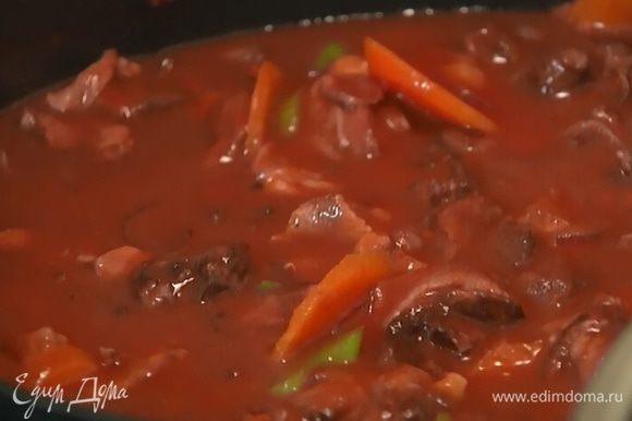 К обжаренным овощам выложить мясо, добавить томатную пасту, влить сохраненный маринад и протертые помидоры. Когда масса начнет закипать, накрыть крышкой и тушить на медленном огне 1–1 1/2 часа.