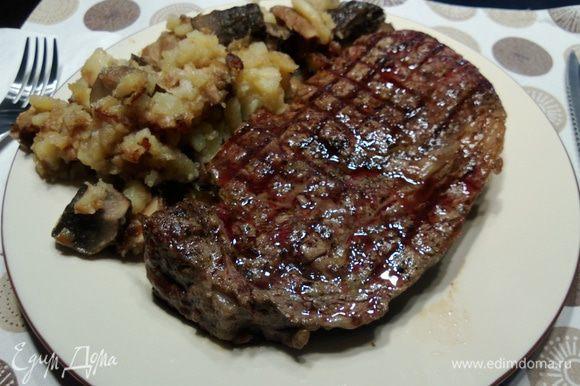 Выкладываем мясо на тарелки, добавляем картошечки с грибами.