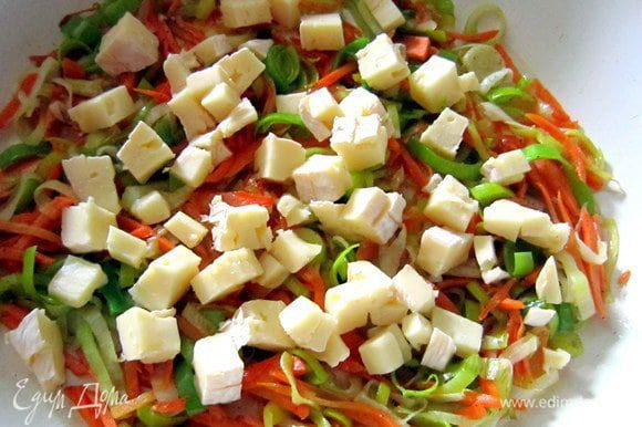 Сыр нарезать небольшими кубиками. Половину сыра добавить в сотейник к овощам. Посолить, поперчить по вкусу и перемешать.