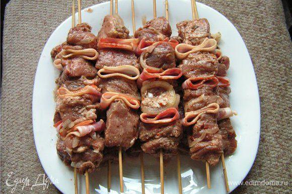 Мясо нанизать на шпажки, чередуя с беконом (полоску разрезать на две части, каждую половинку свернуть пополам)