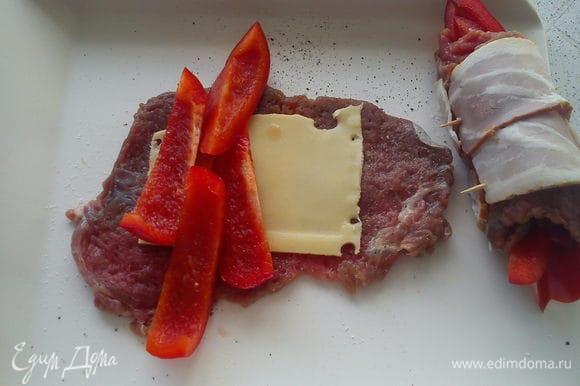 Пластинку сыра и нарезанный полосками перец выложить на мясо. Свернуть рулетик так, чтобы перец выглядывал с обеих сторон. Обернуть рулетик беконом и скрепить зубочисткой