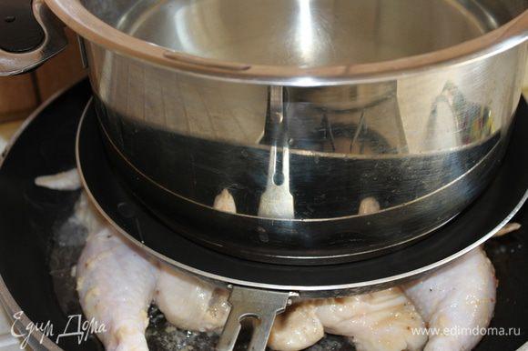 После маринования смахнуть с цыпленка остатки маринада (иначе будет гореть) и уложить его на сковороду. Сверху прикрыть другой сковородой с меньшим диаметром (можно и без нее) и поставить еще большую кастрюлю с водой (для утяжеления). Поскольку я готовила двух цыплят, мне пришлось жарить их сразу на двух сковородах с подобным сооружением одновременно. В это время необходимо включить духовой шкаф, чтобы он разогрелся до температуры 200 градусов