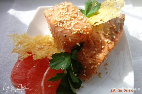 Готовую рыбу выложить на тарелку, чтобы чуть полежала, подавать теплой, украсив зеленью, кунжутом и сырными чипсами.
