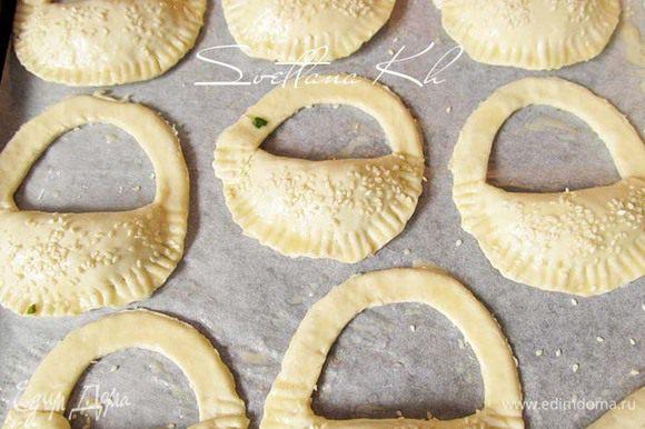 Пирожки смазать яйцом и посыпать кунжутом. Выпекать в духовке до готовности.