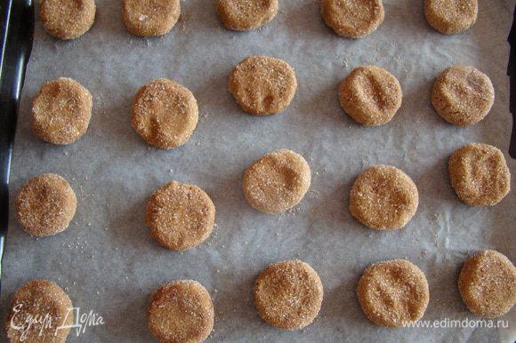Скатываем шарики весом около 15-20 граммов каждый, обваливаем в сахаре, кладем на пергамент, немного приплюскивая