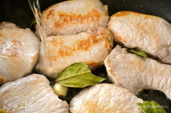 Добавить к мясу белое вино, лавровый лист и чеснок.