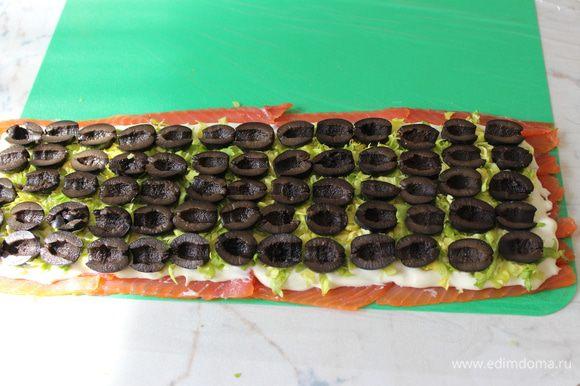 Оливки разрезать пополам и выложить их равномерно по всей поверхности