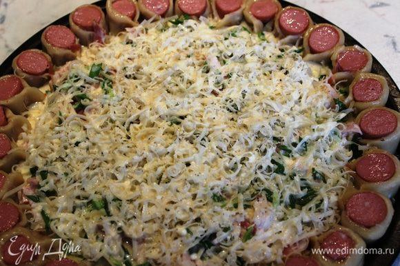 Залить соусом середину пиццы...Смазать маслом срезы сосисок...Поставить в разогретый духовой шкаф на нижний уровень (для того, чтобы снизу образовалась корочка в то время, как верх запекается....иначе верх приготовится быстрее основы и сгорит)