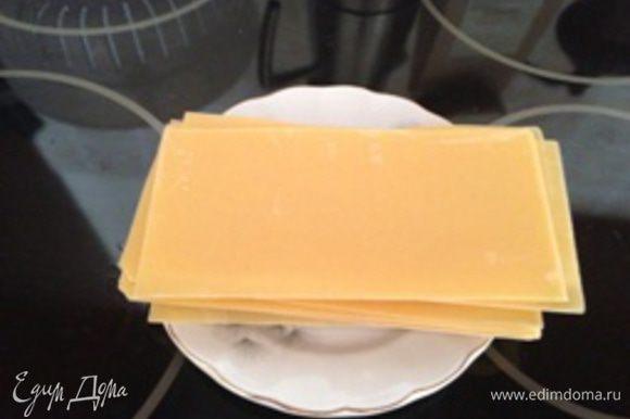 Сотейник или сковороду с высокими бортами (сотейник или сковорода удобнее) наполнить водой наполовину, довести до кипения, добавить 2-3 ст.л. растительного масла (можно использовать кастрюлю). После закипания отварить листы для лазаньи до состояния полуготовности 5-6 минут (альденте). Листы для верхнего слоя лазаньи можно варить подольше, чтобы при запекании корочка не была излишне жесткой. Листы отваривать небольшими порциями по 5-6 листов во избежании их слипания. По готовности первой партии, выложить на дно формы для запекания (или в мультиварку). ВНИМАНИЕ: собирайте лазанью одновременно с отвариванием листов - отваренные листы лучше сразу укладывать в форму для запекания во избежание их пересушивания и слипания.