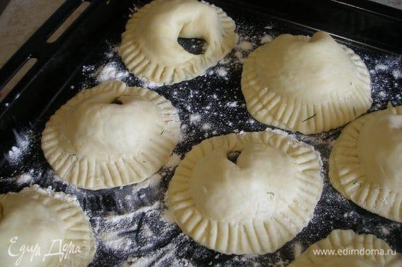 Противень присыпать мукой, выложить на него пирожки и выпекать в духовке 20-25 минут при 180 градусах. Подавать с острым соусом или сметаной с зеленью и чесноком.