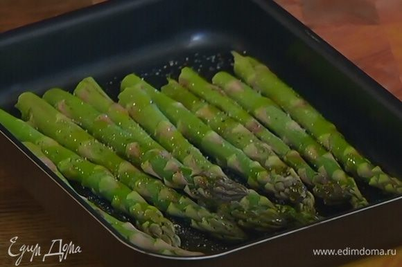 Стебли спаржи, удалив грубую часть, выложить в небольшой глубокий противень, посолить, поперчить, сбрызнуть оливковым маслом, перемешать и отправить в разогретую духовку на 7–10 минут.