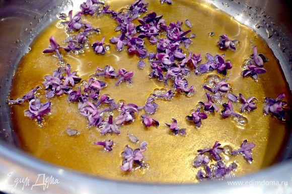 Пятое соцветие сирени промываем, обсушиваем и отделяем от него цветочки. 50 г сахара растапливаем в сотейнике с толстым дном, сироп приобретет янтарный оттенок. Добавляем цветы сирени и выливаем сироп на противень, застеленный пергаментной бумагой. Даем застыть.