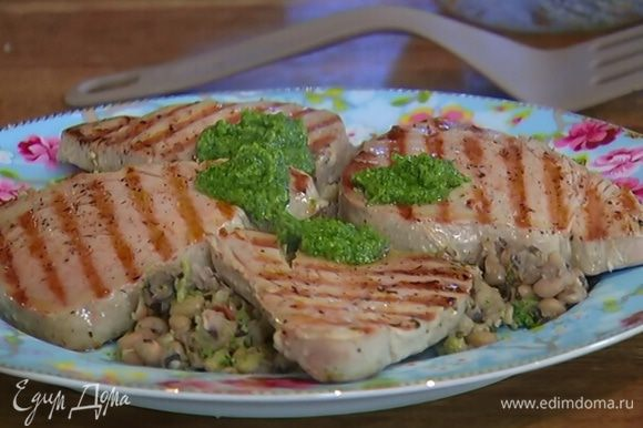 На рыбные стейки выложить понемногу соуса песто, посыпать оставшейся петрушкой и подавать с фасолью и кусочками лимона.