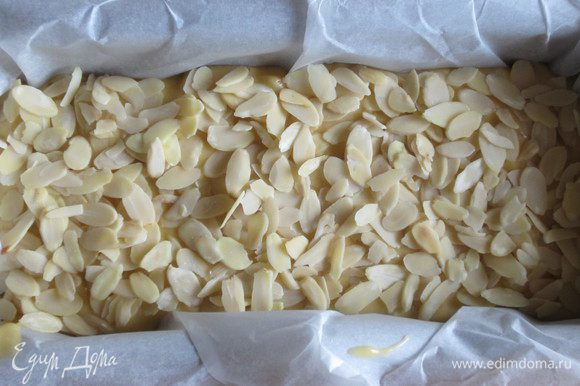 Выложить тесто в форму с пергаментом,посыпать миндальными лепестками и выпекать в разогретой до 180°С духовке 35-40 минут.