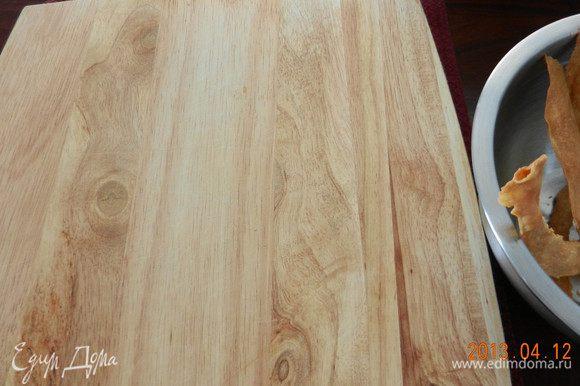 7- На коржи ложите не тяжелый груз (я использовала деревянную дощечку), чтобы они распрямлялись. Пока первый корж подрумянивается, раскатывайте следующий. Перед тем как ложить следующий корж для раскатывания, дайте листу остыть. Хорошо иметь несколько листов для выпечки, дело пойдет намного быстрее. В итоге у вас получится 12 коржей под пресом и отдельно - излишки.
