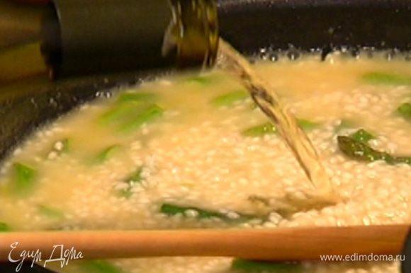 Влить к рису со спаржей 1–2 половника горячего бульона (не перемешивать!), затем добавить оставшееся вино, еще один половник бульона, перемешать и готовить еще примерно 15 минут.