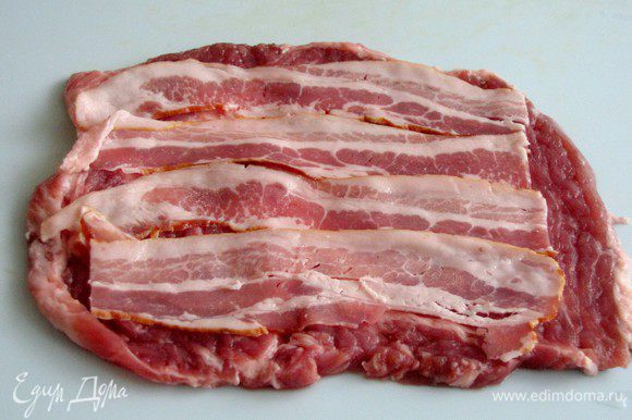 Ломтик отбитого мяса посолите и поперчите. Выложите на него бекон. Если бекон достаточно соленый, то мясо можно не солить.