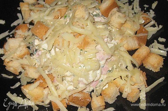 В порционную тарелку выложить салат горкой, посыпать сыром и сухариками.