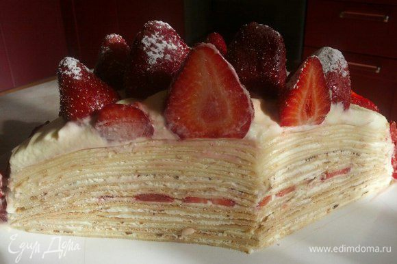 Нанесите немного крема между блинами и по всей поверхности снаружи. Украсьте тонко нарезанной клубникой и присыпьте сахарной пудрой. Поставьте в холодильник на 1-2 часа, чтобы торт затвердел.