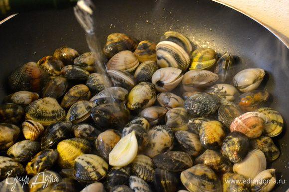 Выложить на сковороду моллюсков. Потряхивая сковороду, дать им обжариться в подготовленном масле. Буквально 1 минуту. Затем добавить стакан белого вина и накрыть сковороду крышкой.