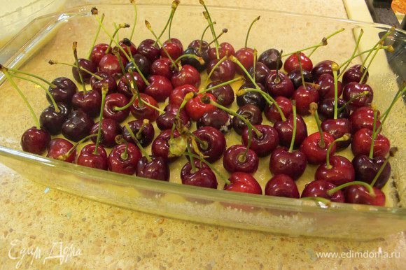 Уменьшить духовку до 170С. Черешню помыть, обсушить и выложить поверх схватившегося теста, прямо с хвостиками. Укладывайте ягоды плотно друг к другу, так как когда вы зальёте их тестом при расстоянии между ними они попадают (хвостики).